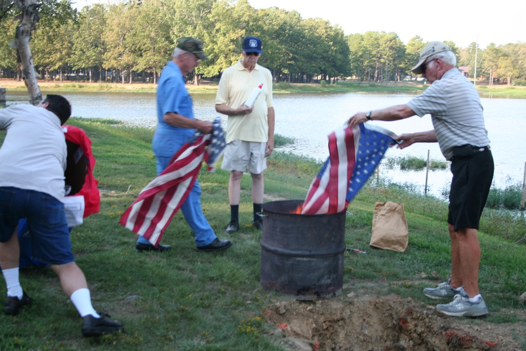 Bill Page lays a flag on the fire as Ron Milazzo gathers others. Jim Alberson looking on