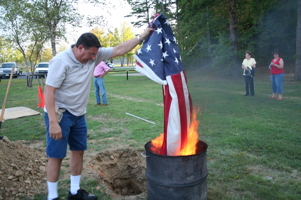 Ron Milazzo holds an extra large flag over the fire